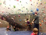 GROMS AND GEEZERS CLIMB SIDE BY SIDE AT THE BEND ROCK GYM.