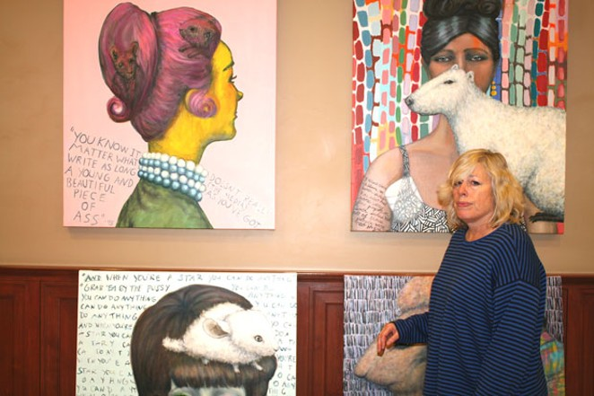 Paula Bullwinkel prepares to remove paintings from the wall of Franklin Crossing, after complaints that the portion of the paintings containing quotes from the 45th president were too offensive. - NICOLE VULCAN