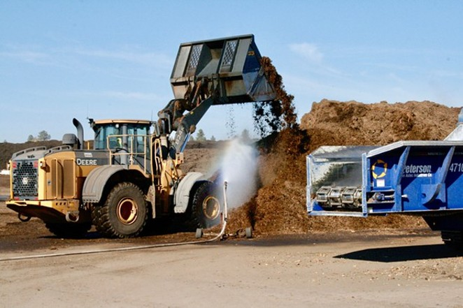 An employee stirs the pile of compost at the Knott Landfill in Bend. - CHRIS MILLER
