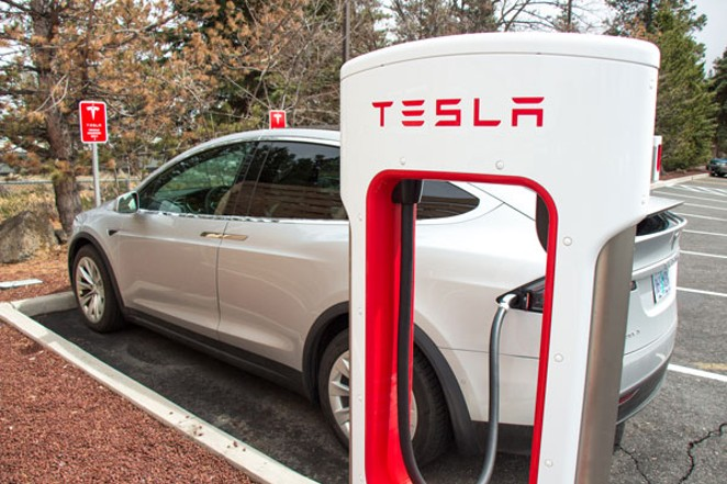 A Tesla charges at a charging station in the Fred Meyer parking lot in Bend. - KEELY DAMARA