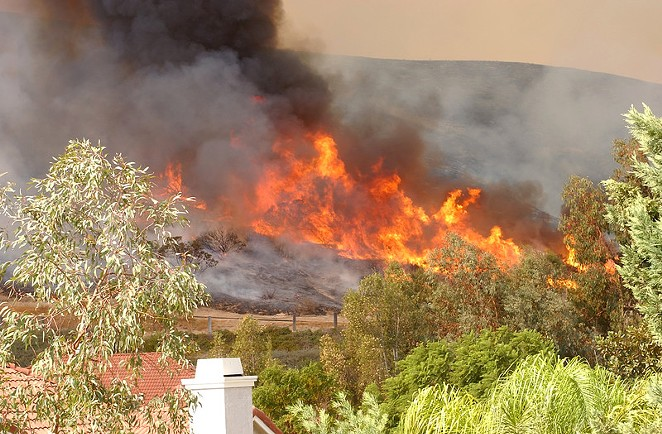 Wildfire burns through a neighborhood in California. - CANSTOCKPHOTO.COM