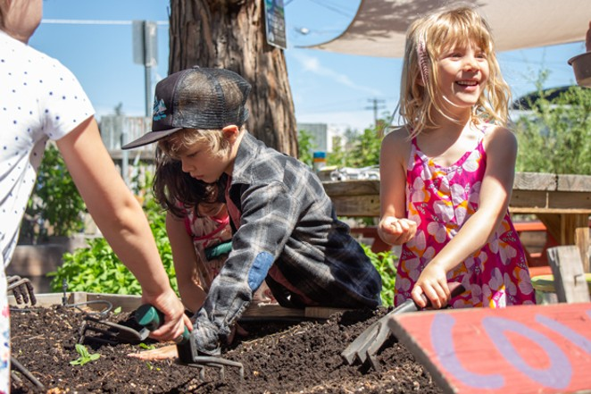 Jude Thomas, left, and Grace Warne help plant seeds in the Kansas Avenue Learning Garden June 5. - KEELY DAMARA