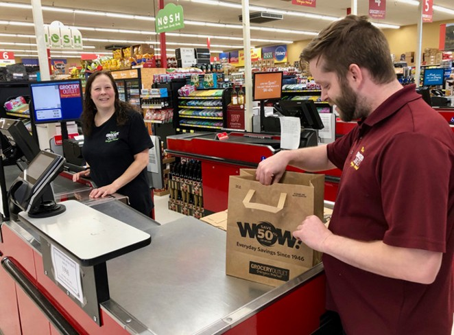 Grocery Outlet Manager, Blake Shappell bags a customer's purchase in a recycled paper bag. Starting Jan. 1, 2020, people that don't bring their own reusable bags to the grocery store may be charged 10 cents for a bag. - CHRIS MILLER
