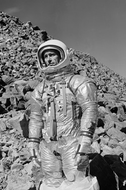 In 1964, Astronaut Walter Cunningham, in his pressurized suit, climbs a slope at the obsidian flow fields near Paulina Lake. - COURTESY NASA