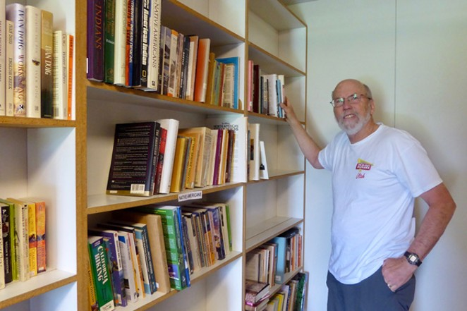 Friends of the Bend Libraries volunteer Tom Carroll places books on the donated shelves in the group's 