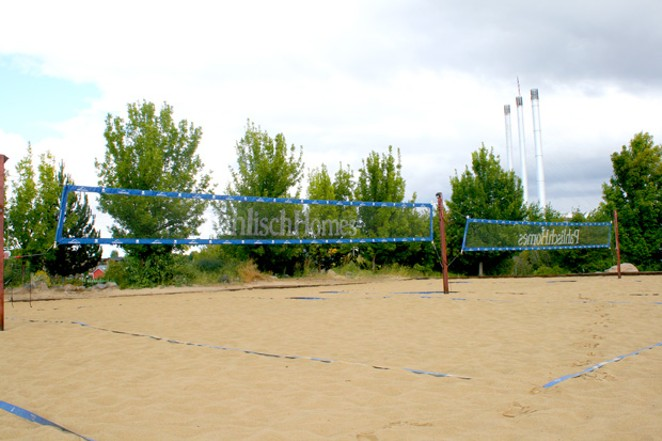 "The iconic ""stacks"" of the Old Mill District loom over the sand volleyball courts Monday. - NICOLE VULCAN"