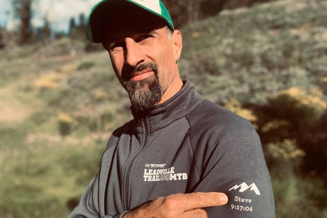Heinemann points to a dedication to his brother on his finisher's jacket, noting his time in the 100-mile mountain bike race. - SUBMITTED