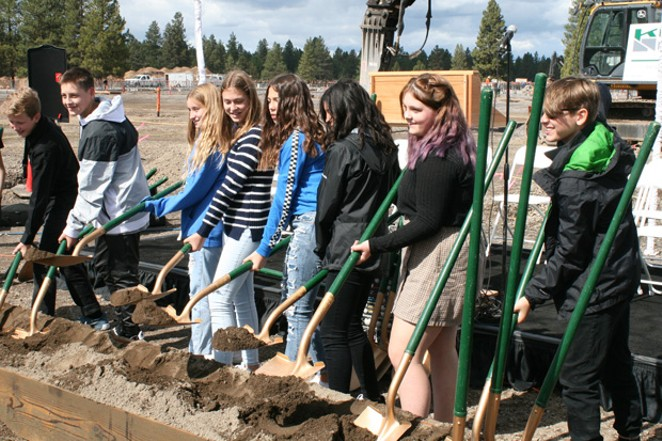 Bend-La Pine Schools students take their turn hoisting the golden shovels at the groundbreaking for the new high school in southeast Bend Sept. 19. - ISAAC BIEHL
