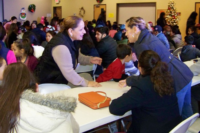 An overflow crowd of Latino families showed up for a free Christmas dinner at the Senior Center in Redmond in December 2018, hosted by the Latino Community Association. - DENISE HOLLEY