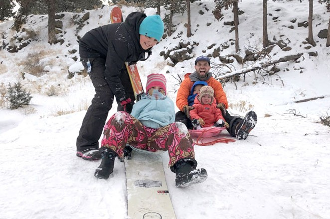 When the snow falls and you want to go sledding, sometimes you have to get creative! Bend kids Makoa and Maile Vidinha use a snowboard, sans bindings, to sled down the hills at Al Moody Park over the Thanksgiving weekend. At right, twins Gus and Eva Jones get their first sled ride from their dad, Matt Jones. - NICOLE VULCAN