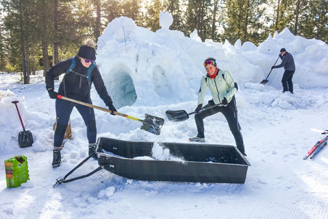 Volunteers work on the giant snow dragon. - JOSH COOK