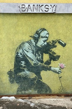"""The best known Banksy art in Park City, """"Camera Man and Flower,"""" is located in an alley right off Main Street downtown. It appeared during the 2010 festival, coinciding with the street art documentary, """"Exit Through the Gift Shop,"""" directed by the underground graffiti artist. It has been framed and covered with bullet-proof glass for protection. - COURTESY FLOY SITTS"""