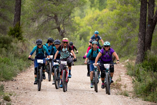 Members of Ladies All Ride joyfully bike through the Oregon woods. - JEFF CLARK