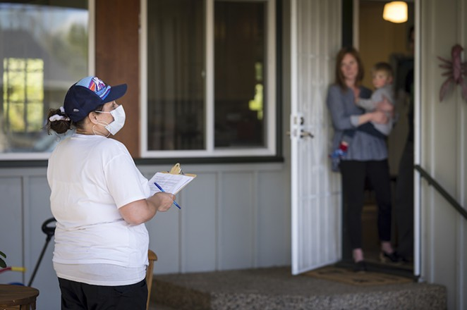 A field staff member for OSU's TRACE-COVID-19 project stands at a distance from the woman she is about to ask to volunteer to take the test. Participants leave completed tests outside. - OREGON STATE UNIVERSITY