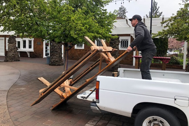 Outdoor seating is a viable option for restaurants to offer sit-down service as the the commuity enters Phase One. Here, Dan Baumann, owner of The Commons Cafe & Taproom, sets up a picnic table outside the Rademacher House . - NICOLE VULCAN