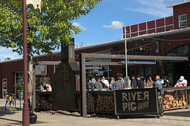 Bar-goers take advantage of nice weather on the River Pig Saloon patio. - CAYLA CLARK