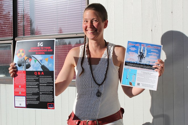 Katrina Rose, 39, passes out posters and fliers last Wednesday to get the word out about the health impacts of 5G cell towers. - LAUREL BRAUNS