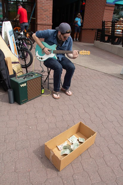 Street Performer Taylor Levin, pictured at left, - seranades shoppers at the Wednesday farmers market in downtown Bend. - KYLE SWITZER