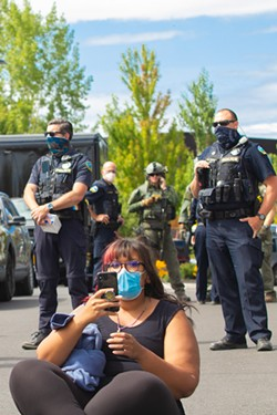 Bend Police officers flank a protester at the scene of the ICE bus standoff Aug. 12. - KYLE SWITZER