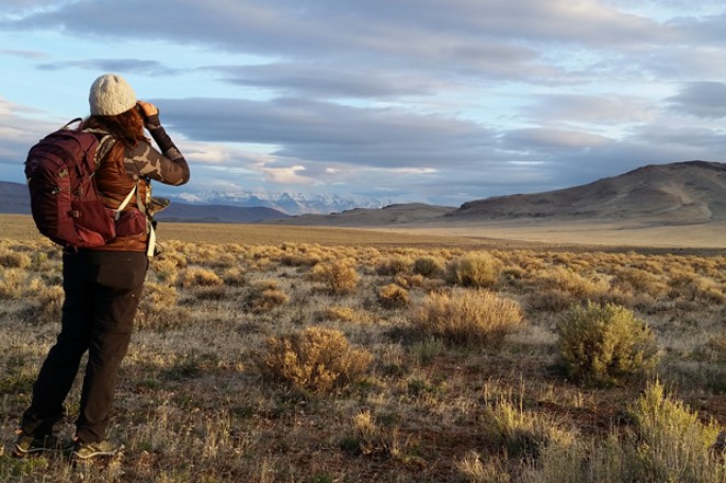 A day hiker scans for wildlife in the Oregon Outback. - DAMIAN FAGAN