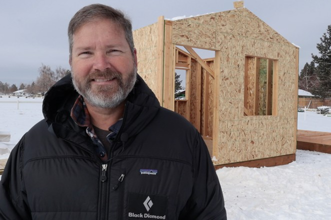 Bend Heroes Foundation President Erik Tibiason stands in front of one of the tiny homes under construction. - DARRIS HURST