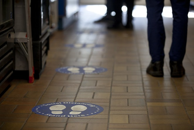 People stand besides floor stickers that encourage social distancing. - GOTOVAN ON FLICKR