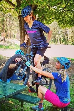 Riding over rocks and obstacles are the heart of the mountain biking sport, as practiced on a picnic table. - COURTESY LADIES ALL RIDE