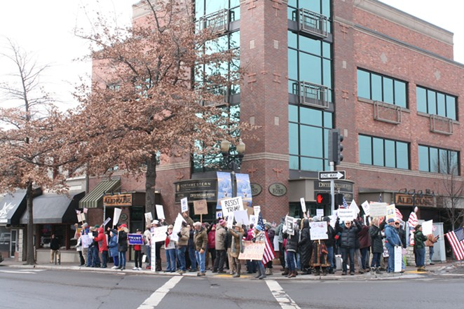 Demonstrators in front of Rep. Greg Walden's Bend office Tuesday. Ongoing demonstrations are scheduled for Tuesdays at 11:30 am. - NICOLE VULCAN