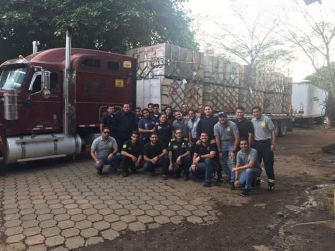 """Condega Fire Chief Jaime Delgado Cultura and a crew of Nicaraguan """"bomberos""""—firefighters—stand in front of the equipment donated by the Bend Fire Fighter's Foundation. - COURTESY BEND FIRE FIGHTER'S FOUNDATION"""