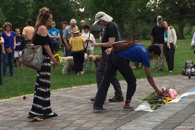 Attendees at the Bend vigil laying flowers - MEAGHAN BULL