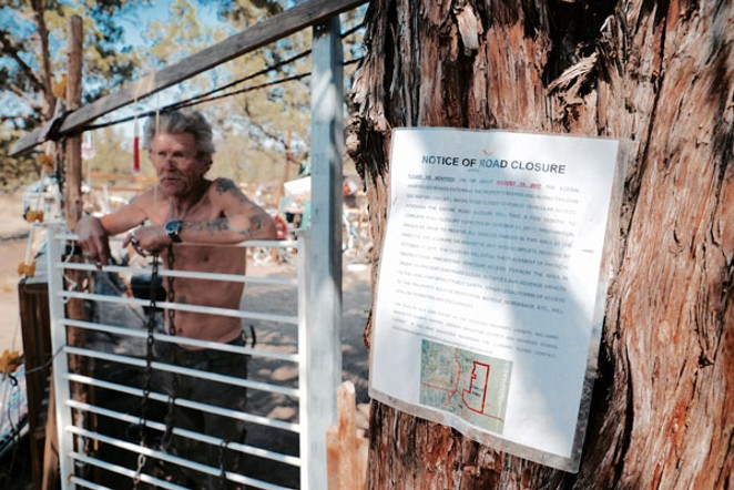 Hawk, a 6-year resident stands out front of his camp with the posted notice of closure - CHADD TULLIS