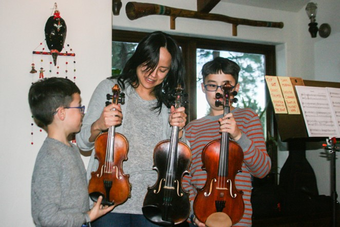 It's all in the family: Brothers Ezra and Nicolas Oncken, of Sisters, discuss the many sizes of violins with their mom, Akiko, in their home, just before evening practice. - JIM ANDERSON