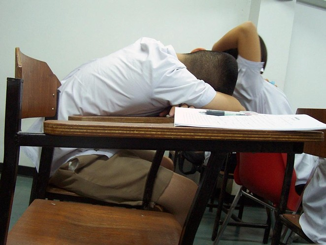A student sleeps at his desk in Thailand. - LOVE KRITTAYA