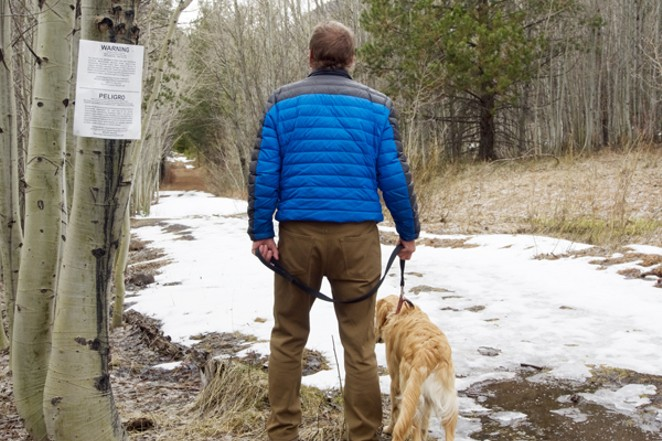 Chris Morrison and his golden retriever Sunny walk past the USDA sign warning hikers of traps set in the marshy area along Tumalo Creek off the trail to Tumalo Falls. - CHRIS MILLER
