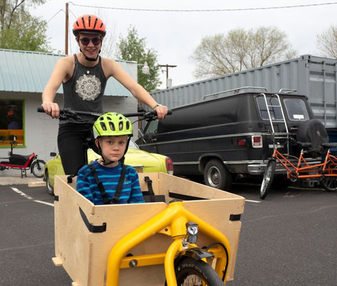 Willow Hamilton rides Aidan Miller around in a Bakfiets-style bike in the parking lot of Bend Electric Bikes. - CHRIS MILLER