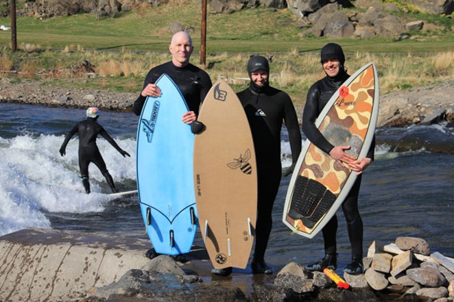 From left, Conway Bixby, Chris Caldentey and Kea Eubank hug their handcrafted river surfboards. - K.M. COLLINS
