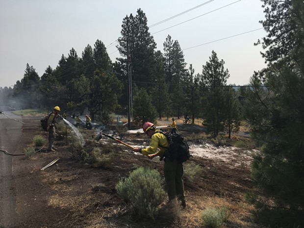 USFS crews mopping up small fire on Century Drive. - DAN DERLACKI.