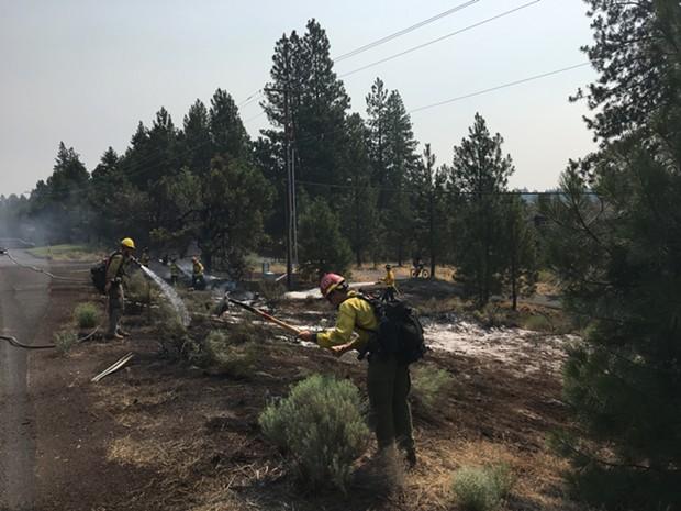 USFS crews mopping up small fire on Century Drive. - DAN DERLACKI.