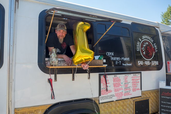 Scott Byers hangs out the window of his Ronin food cart. - CHRIS MILLER