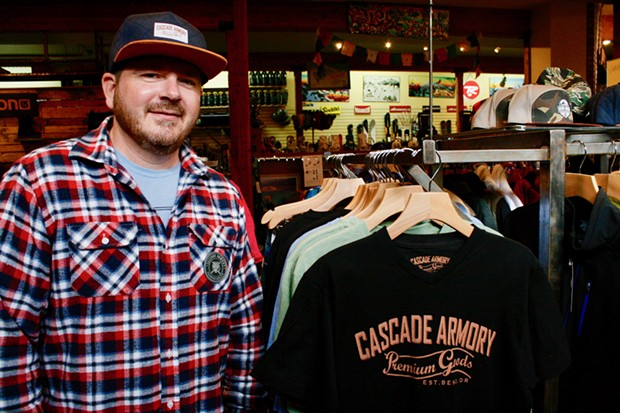 Cascade Armory's Alex Short stands next to his clothing line at Skjersaa's in Bend. - CHRIS MILLER