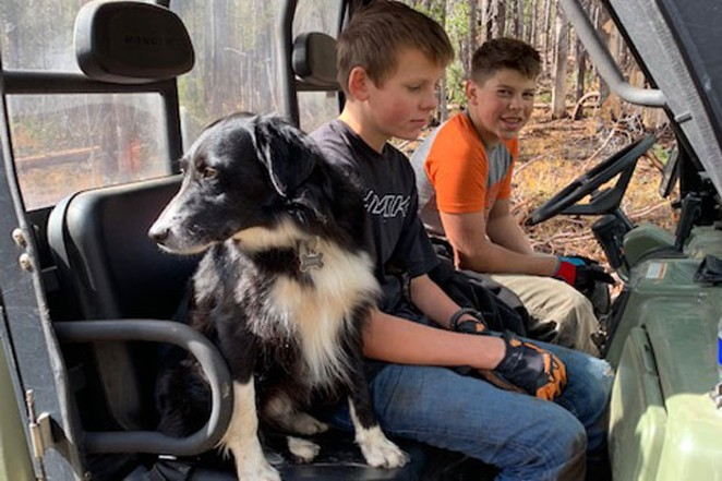 Matthew Maul and Ryder Fasset taking a break from moving heavy logs out of a trail. - MOON COUNTRY SNOWBUSTERS