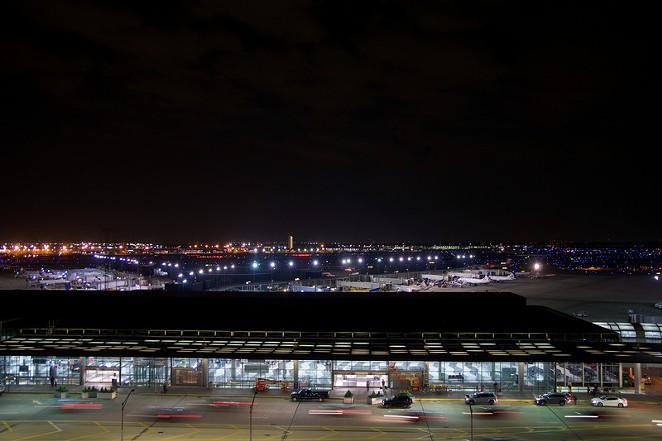 Outside of Chicago O'Hare International Airport at night with some cars and airplanes at the terminal. - CANSTOCKPHOTO.COM