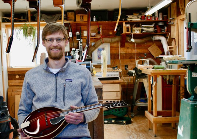 Andrew Mowry sits with a mandolin in his shop in Northeast Bend. - CHRIS MILLER
