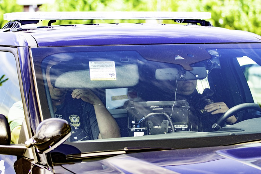 A man wearing an ICE badge, at left, sitting inside a Bend PD patrol vehicle Aug. 12. - KYLE SWITZER