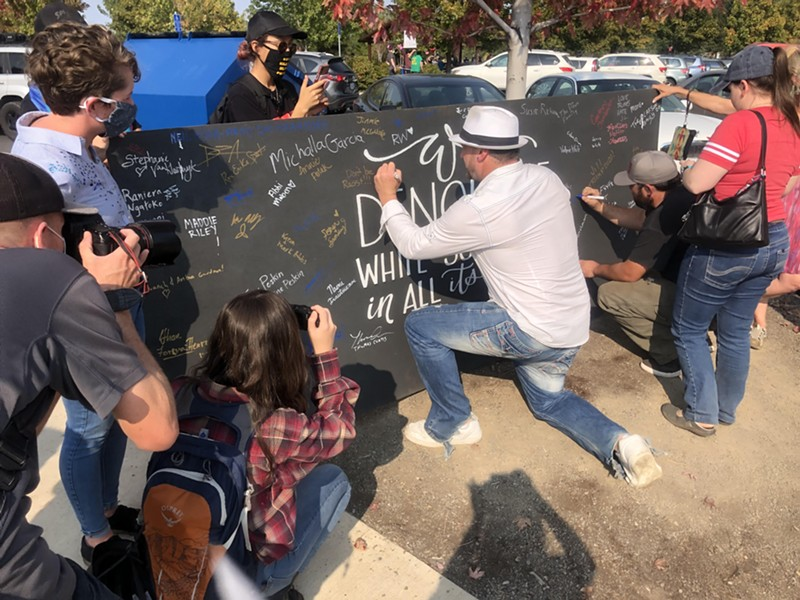 """Nicholas Dieringer, who planned a pro-Trump rally and cruise in Bend on Oct. 3, signs a chalk board which reads """"I denounce white supremacy and all its forms."""" For hours, both BLM activists and the pro-Trump group co-existed at the park in relative harmony. - COURTNEY CHRISTENSON"""