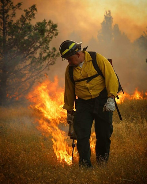 Mike Leecy, Confederated Tribes of Warm Springs Supervisory Timber Presale Technician, uses a drip torch to burn black line; a containment line created to burn/remove the short grasses from the path of the fire. - EDWARD HEATH