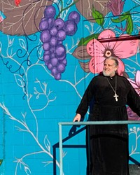Father Damian Kuolt in front of the colorful mural on the side of the bookstore, painted by artist Nicole Fontana Campbell in 2017.