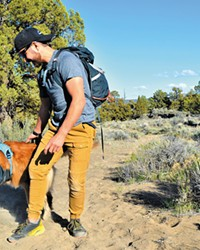 """Heather Downing-Barrier shared this photo of her husband, Nick, and their Saint Bernard mix, Arwen, in the Oregon Badlands Wilderness. Heather said Arwen braved a lot of health challenges this year, and showed the couple that """"there's still happiness to be had with a daily walk, some good food in our bellies, and nightly cuddles."""""""