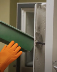 In a screengrab from a video issued by St. Charles, pharmacist Tyler Larson demonstrates the use of the freezer used to store and administer the Pfizer-BioNTech COVID-19 vaccine.