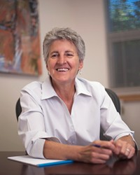 Dr. Becky Johnson sits at her desk for a photo taken for Oregon State University's College of Business Magazine.